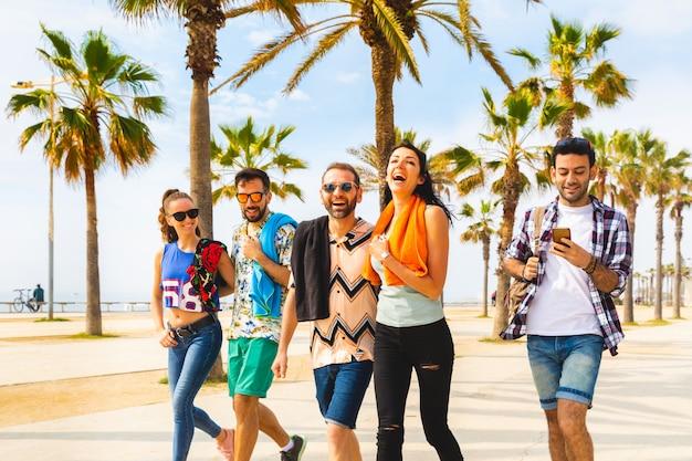 海辺で幸せな友達がバルセロナを歩く