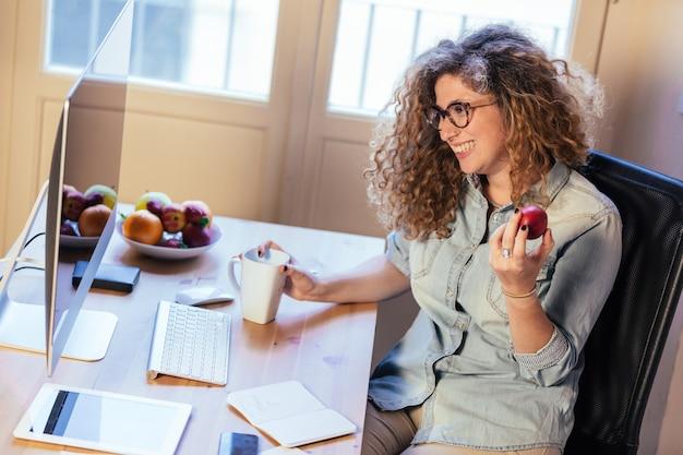 Молодая женщина работает на дому или в небольшом офисе