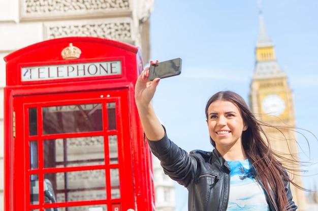 電話ボックスとビッグベンのロンドンの若い女性