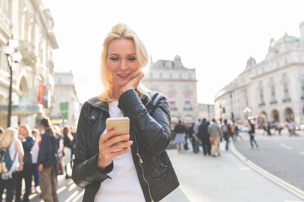ロンドンのスマートフォンを見て大人の女性