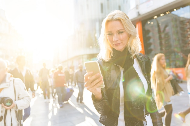 ロンドンでスマートフォンを見ている金髪の女性