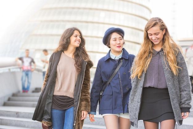 ロンドンを歩く女の子の多民族グループ