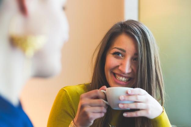 Две женщины в кафе, улыбаясь и глядя друг на друга