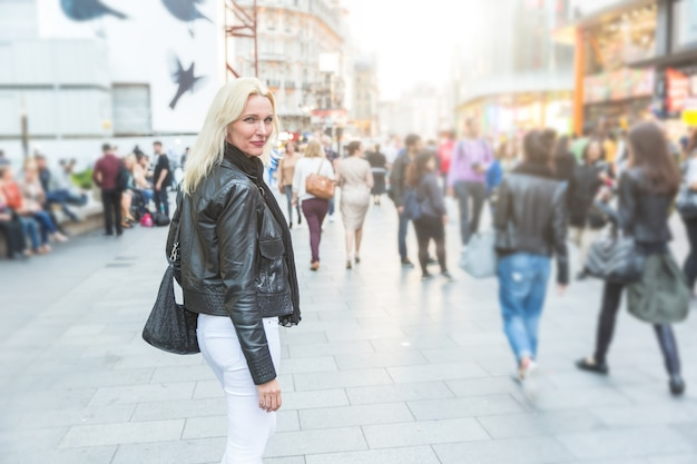 混雑したロンドンの通りを歩いて美しい女性。