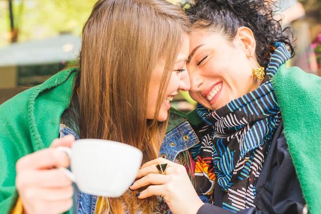 コーヒータイムを一緒に共有することに愛の幸せなガールフレンド
