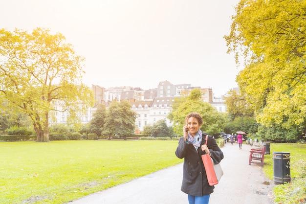 ロンドンの公園で電話で話している若い女性