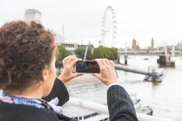 若い女性が彼女のスマートフォンとロンドンのビッグベンの写真を撮る