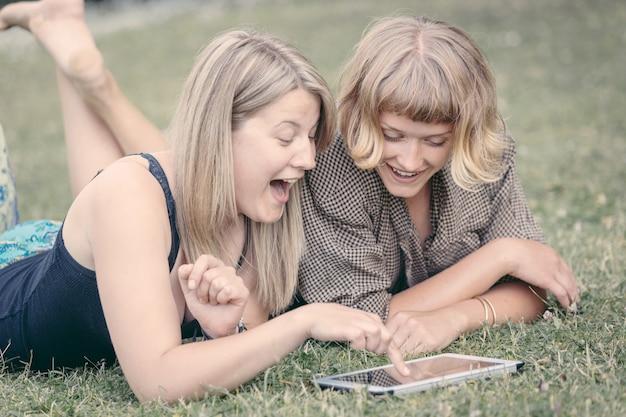 Две русские девушки с помощью цифрового планшета в парке