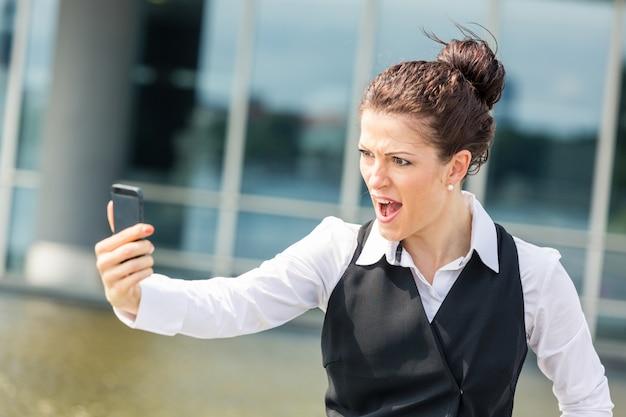 携帯電話で叫んでいる若い実業家