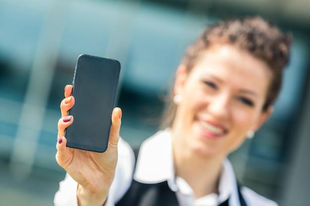 携帯電話を示す若い実業家