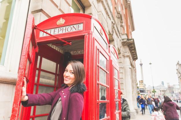 典型的な赤い電話ボックスの前にロンドンの若い女性