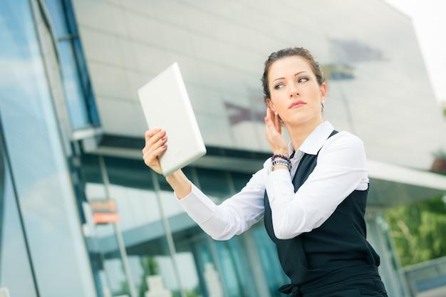 Бизнес-леди с помощью цифрового планшета в качестве зеркала для макияжа