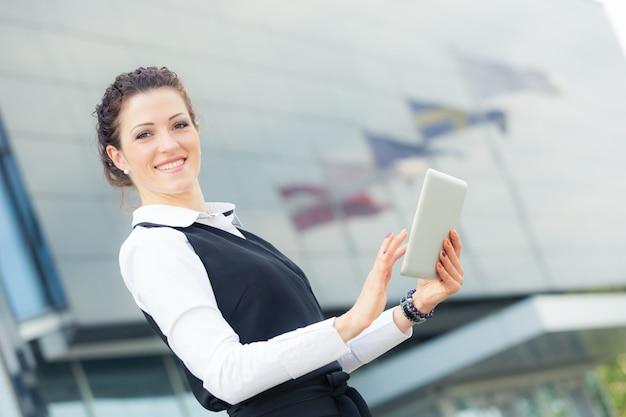 Молодая коммерсантка с цифровым планшетом на финансовом районе