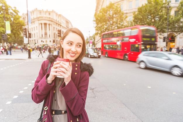 コーヒーを保持しているにぎやかな道のそばに立っているロンドンの女