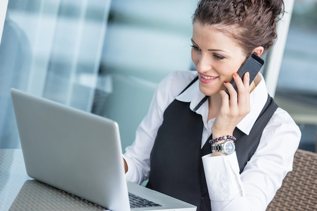 コンピューターと携帯電話を持つ若い実業家