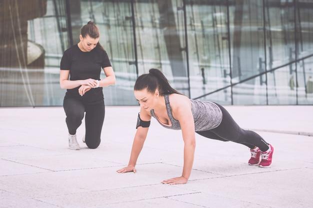 彼女のパーソナルトレーナーと腕立て伏せ運動をしている女性