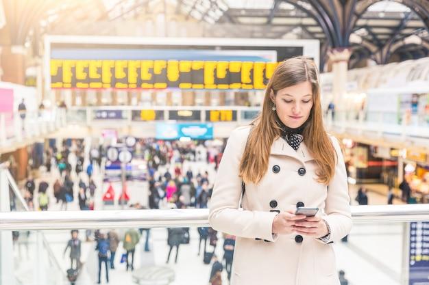 若い女性が駅で彼女のスマートフォンに入力します。