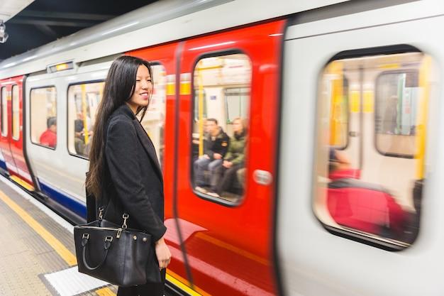 Китайская женщина ждет на станции метро
