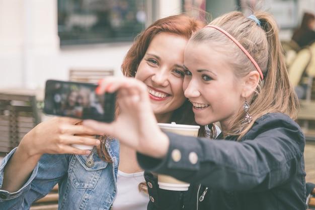 Девушки фотографируют с помощью мобильного телефона
