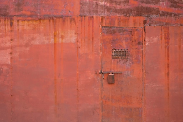 グランジとロックされたドアの背景を持つ古い赤い壁