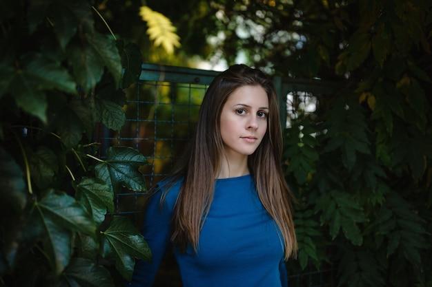 Красивая девушка в синей рубашке с длинным рукавом в осеннем парке