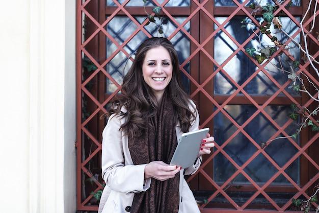 デジタルタブレットを屋外で使う女の子。春か秋。