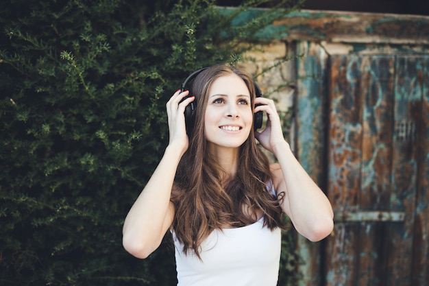 笑顔と屋外のヘッドフォンで音楽を聴く若い女性