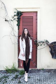 路上でベージュのコートを着た美しい少女