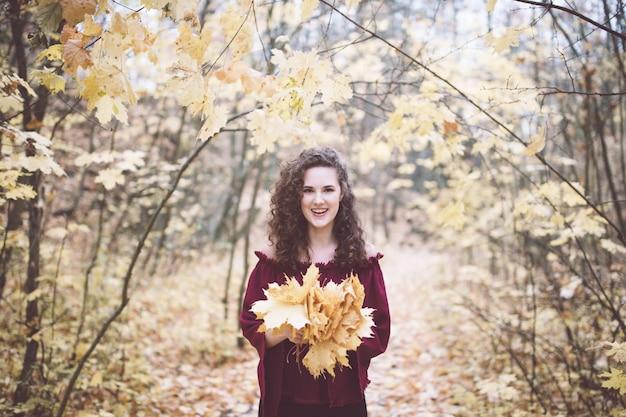 カエデの葉を保持しているアタム公園で幸せな女の子
