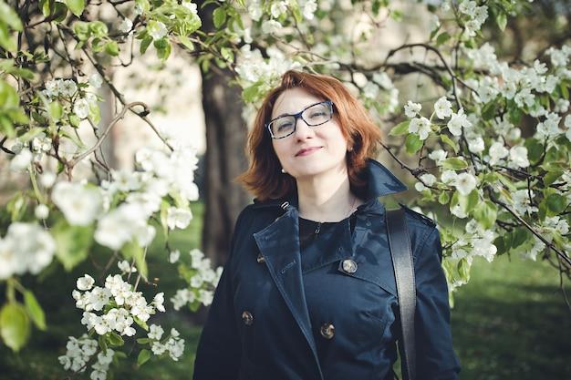 咲く木の下で青いトレンチコートを着た中年の南アルメニアの女性。