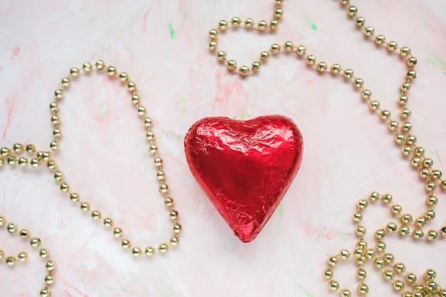 Шоколадное сердце в красной фольге на розовом фоне
