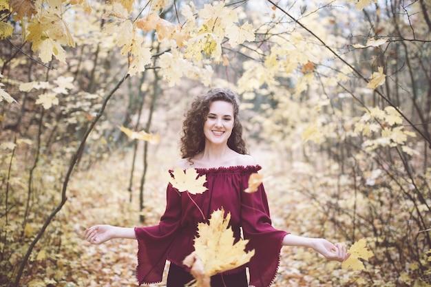 Счастливая девушка в осеннем парке бросает кленовые листья