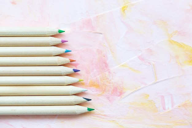 Разноцветные карандаши на розовом фоне