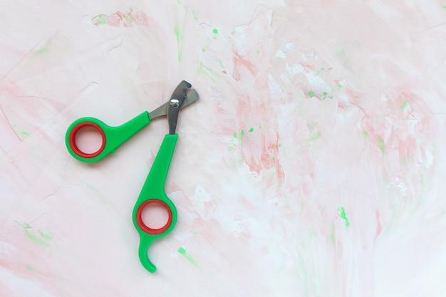 ピンクの壁の猫と犬のためのプロのグリーンペットの爪切り、コピースペース。ペットの世話、猫と犬のトリマーの爪のコンセプト