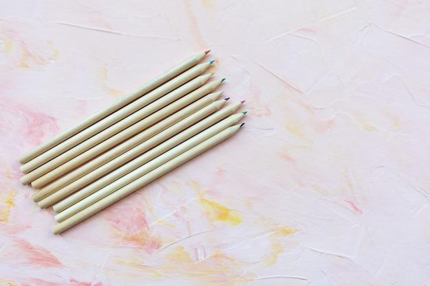 Разноцветные деревянные карандаши на розовой стене. рисование, творчество или вернуться к концепции школы, копировать пространство