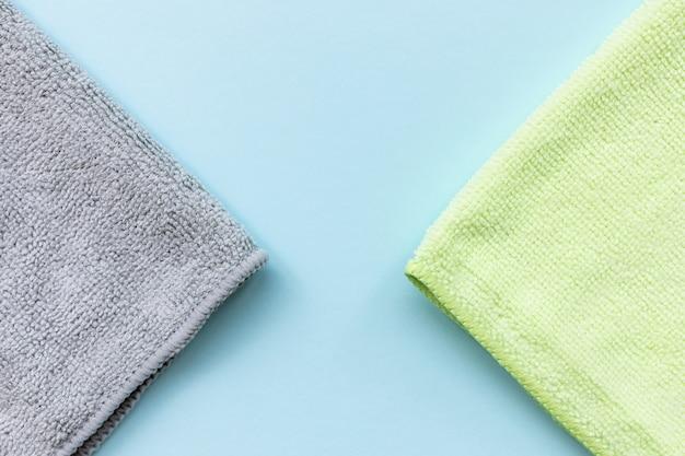 Две новые сложенные ткани из микрофибры для очистки на синем фоне. чистка микро тканевых полотенец для пыли и полировки. концепция бытовых услуг по уборке. закройте, скопируйте пространство