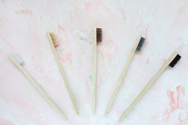 Натуральные деревянные бамбуковые зубные щетки. без пластика и ноль отходов концепции. вид сверху, розовый фон