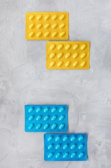 ブリスターパックのさまざまな錠剤のセット。ヘルスケアと医療の概念。クローズアップ、灰色の背景、コピースペース