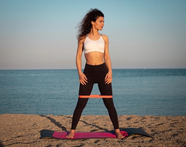 Женщина занимается йогой на пляже