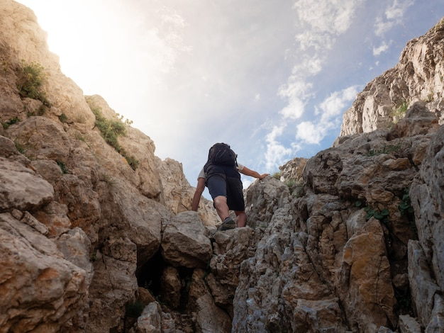 若い男が日没で山に登る。コンセプトの冒険、探検。 (スペイン、カタルーニャ、ペドレフォルカ)