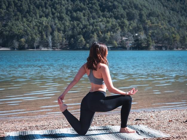 自然に囲まれた湖の横にある屋外でヨガを行う若くて魅力的な女の子。健康的な生活のコンセプトです。