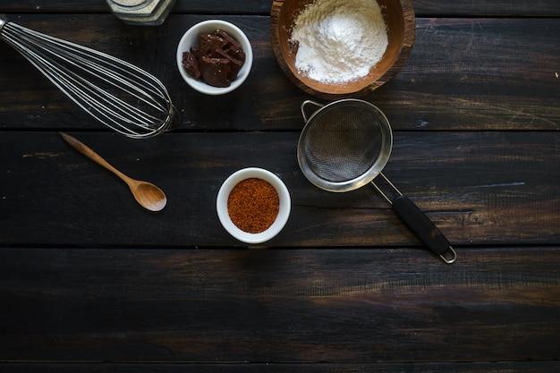Кухонная утварь расставлена случайным образом на темном деревянном столе.