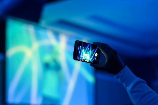 コンサートでスマートフォンを持つ手のシルエット
