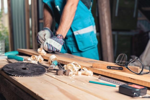 テーブル、手袋、オーバーオールの平面の選択的なフォーカスを持つ男の木工ツール