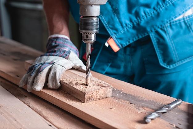Мужчина столяр в комбинезоне и перчатках сверлит деревянную доску крупным планом.