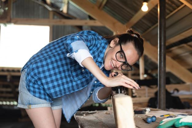 木の板の正面に平面を働く安全メガネの女