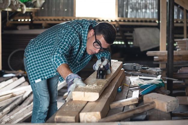 ワークショップで格子縞のシャツとジーンズのプレーニング木製マニュアルの男