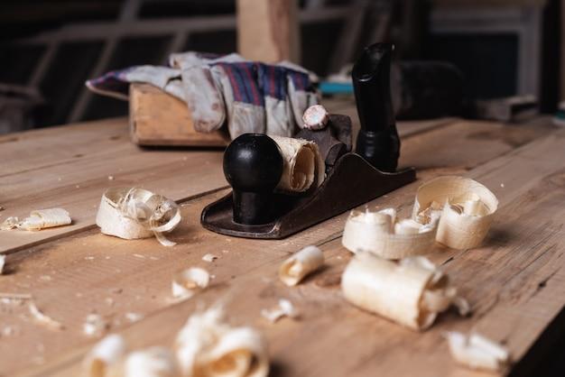 手袋とおがくずと削りくずの木製のテーブルの上の木槌で古いレトロな手かんな