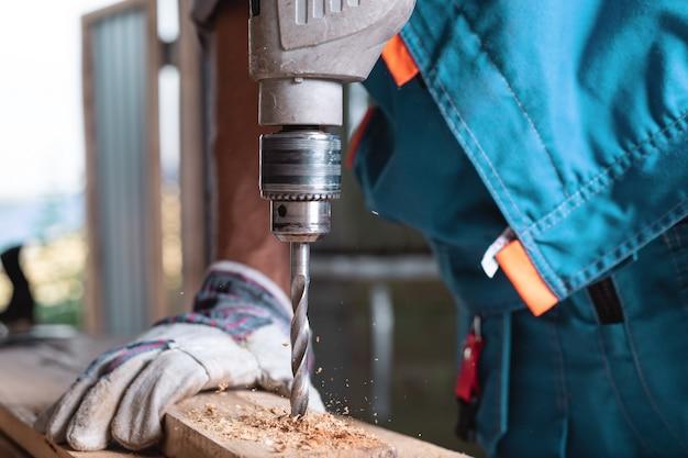 Плотник в комбинезоне и перчатках сверлит деревянную доску в домашней мастерской