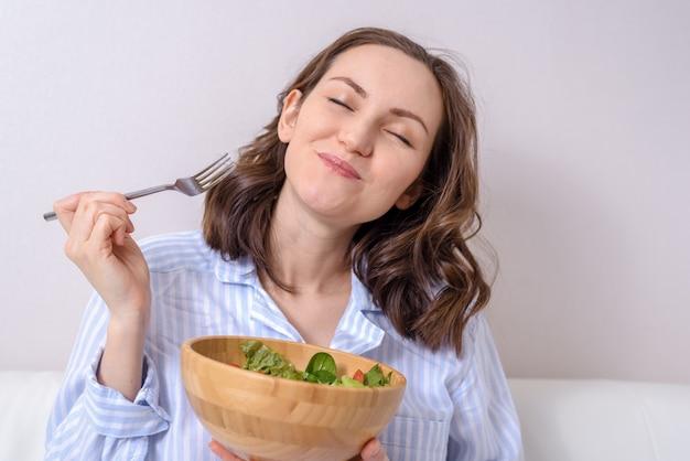 喜びと目を閉じて健康的な野菜のサラダを食べる青いシャツを着た女性のクローズアップ